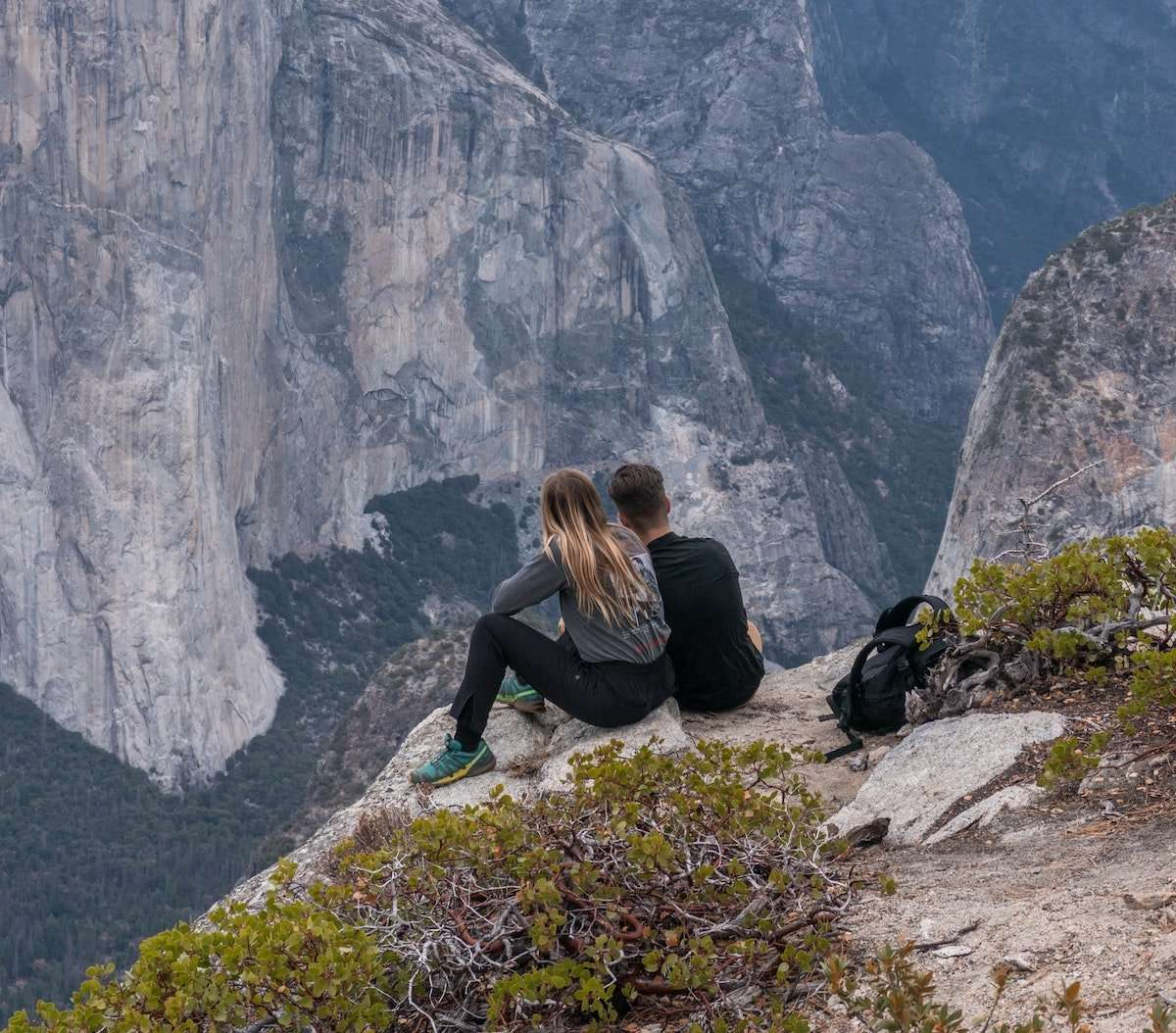 couple hiking in mountains contemplating investment management opportunites