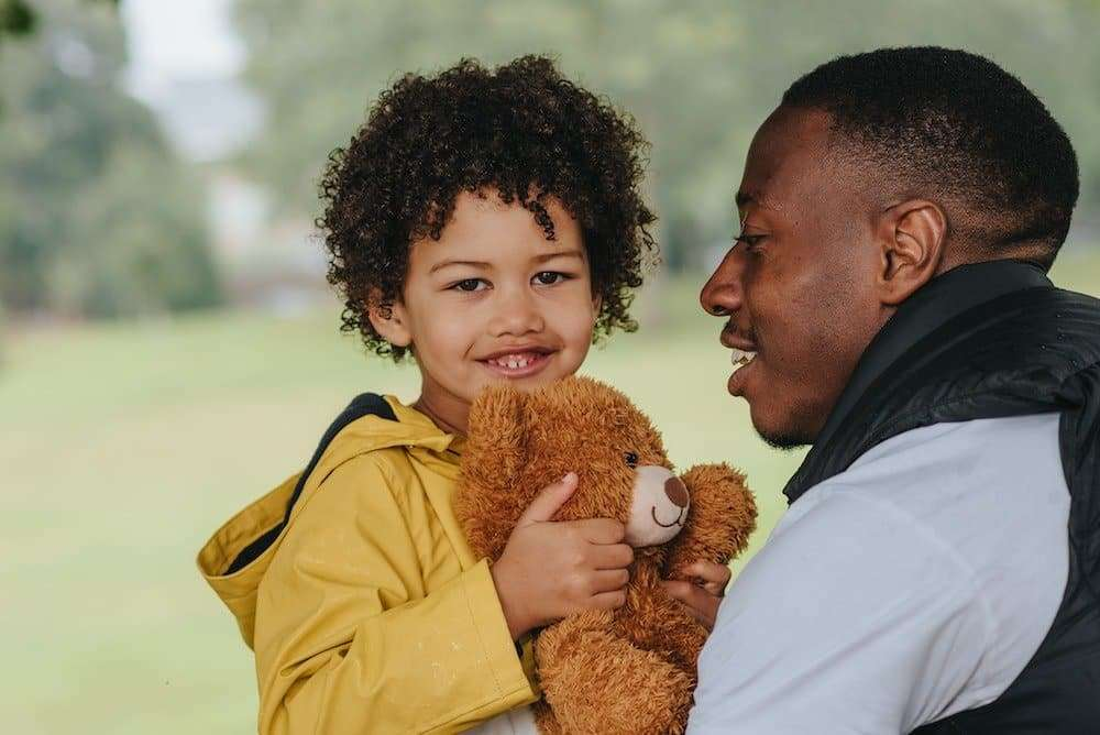 little girl holding a stuffed bear being held by dad contemplating financial future